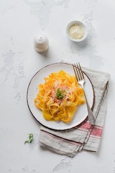 Fettuccine pasta met traditionele italiaanse passat saus en parmezaanse kaas in lichte plaat op oude witte betonnen ondergrond.