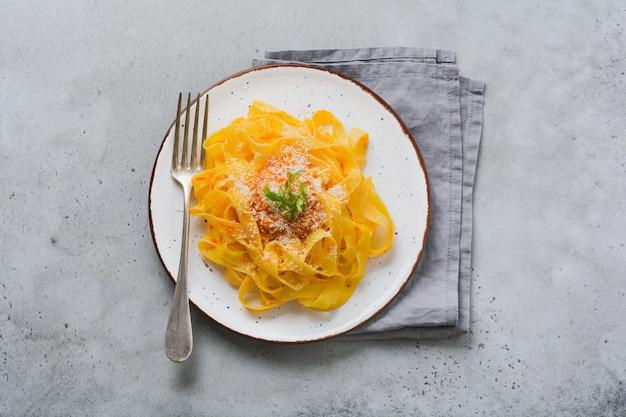 Fettuccine pasta met traditionele italiaanse passat saus en parmezaanse kaas in lichte plaat op oude witte betonnen ondergrond