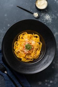 Fettuccine pasta met traditionele italiaanse passat-saus en parmezaanse kaas in zwarte plaat op donkere ondergrond
