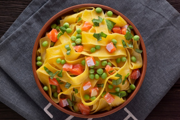 Fettuccine pasta met zalm en groene erwten op een houten tafel in een kom. bovenaanzicht.