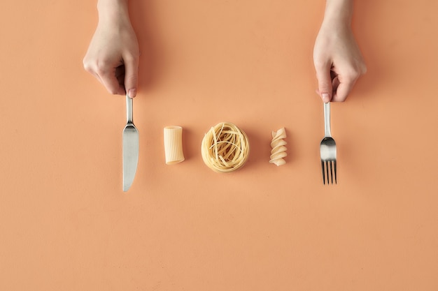 Fettuccine, tortiglioni, fusilli pasta en handen met vork en mes