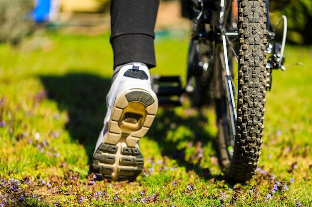 Fiets bij de zomer zonsondergang op het gras in het stadspark. het wiel van de cyclusclose-up op vage de zomerachtergrond. fietsen door de straat om te werken bij zonsondergang in de zomer. fiets en ecologie levensstijl concept.