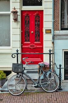 Fiets dichtbij deur van oud huis in de straat van amsterdam