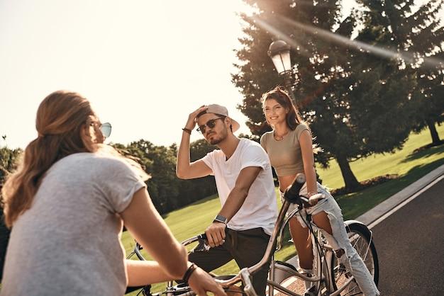 Fiets maatjes. groep gelukkige jonge mensen in vrijetijdskleding die lacht en communiceert terwijl ze samen buiten fietsen