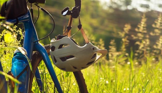 Fiets met een helm die aan het stuur hangt tegen groen gras. detailopname.