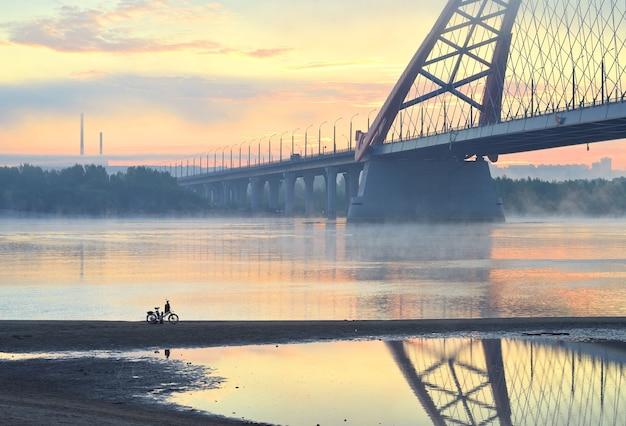 Fiets op het strand. auto bugrinskij brug over de grote siberische rivier ob in de ochtendmist