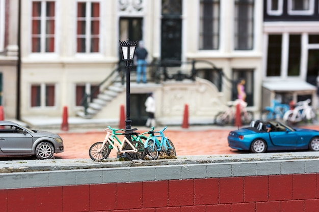 Fietsen bij de lantaarnpaal op stadsstraat, miniatuurscène openlucht, europa. minifiguren met hoge detaling van objecten, realistisch diorama, speelgoedmodel