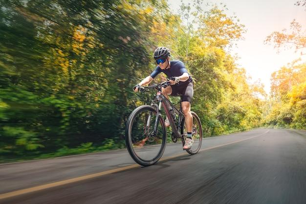 Fietsen mountainbike fietsen mtb op de weg schaduwrijk met bos. mountainbiken atleet kijkt naar de wilde natuur op de berg. extreme sport en mtb, mountainbike downhill of motion concept.