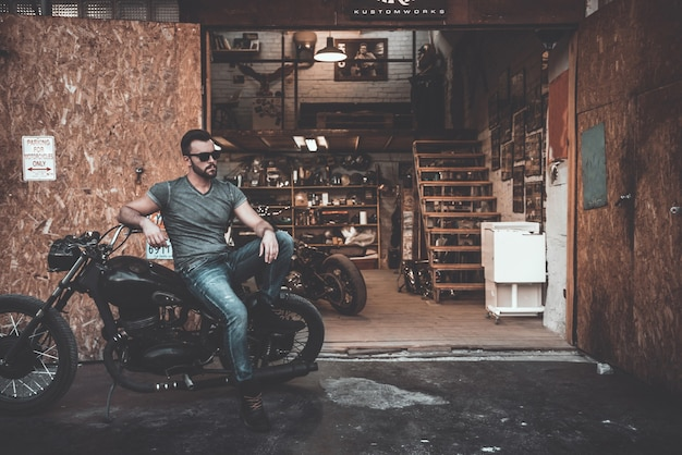 Fietsen zijn niet voor iedereen. knappe jonge man zittend op zijn fiets met motorgarage op de achtergrond