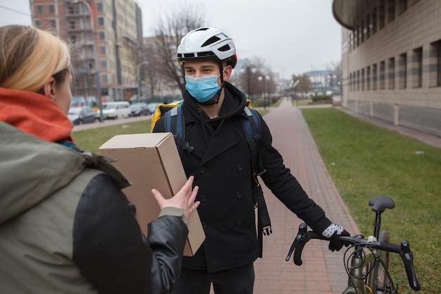 Fietsende koerier die medisch gezichtsmasker draagt, pakket aan een vrouwelijke cliënt levert
