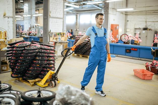 Fietsenfabriek, arbeider draagt een kar met fietswielen. mannelijke monteur in uniform installeert fietsonderdelen, lopende band in werkplaats