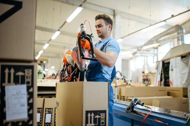 Fietsenfabriek, werknemer pakt tienerfiets in doos. mannelijke monteur in uniform installeert fietsonderdelen, lopende band in werkplaats