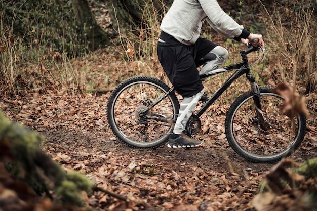 Fietser berijdende fiets op sleep in het bos