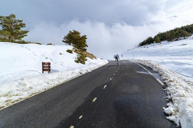 Fietser die besneeuwde hoge bergpas beklimt. la morcuera.