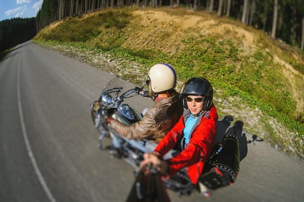 Fietser die zijn motorfiets berijdt op de weg met de passagier