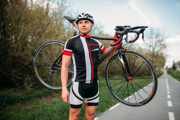 Fietser houdt de fiets op de schouder na het fietsen