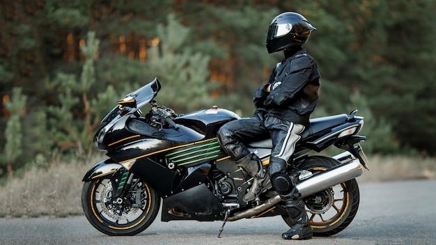 Fietser in helm en lederen beschermingsmiddelen zit op een motorfiets, een sportieve snelle motorfiets