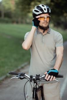 Fietser in sportkleding en helm staat op de weg in het park en kijkt naar de zijkant