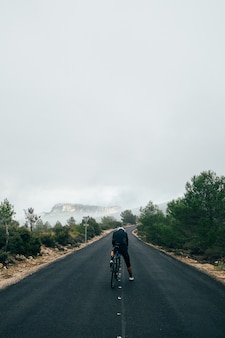 Fietser met een fiets bij zonsondergang in een bergweg