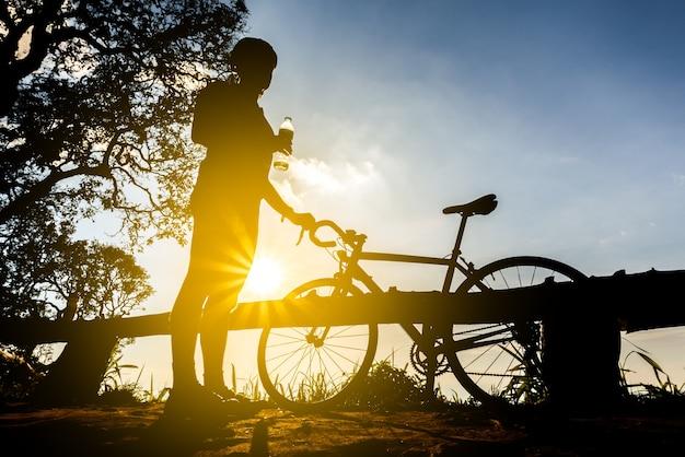 Fietser met een fiets silhouet op zonsondergang hemelachtergrond