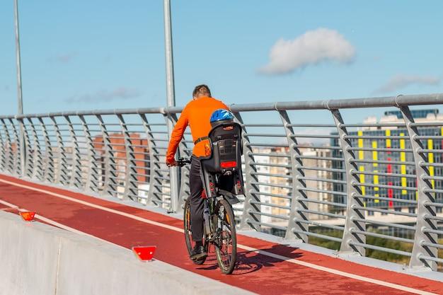 Fietser met kinderstoel en baby. familie in warme kleren fietsen in de stad op de brug. vader met kind rijden fiets.