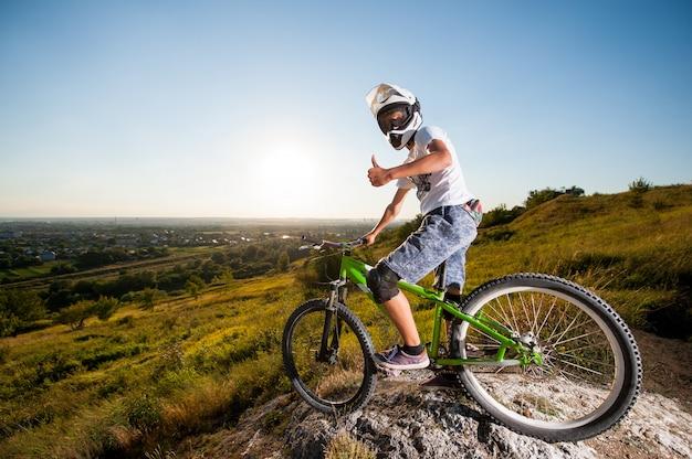 Fietser met mountainbike op de heuvel onder de blauwe hemel