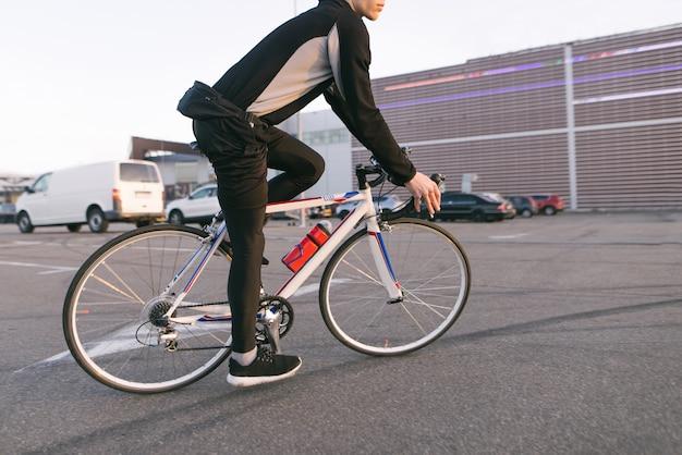 Fietser op een snelle fietstocht, rit op de parkeerplaats, op de achtergrond van het winkelcentrum.