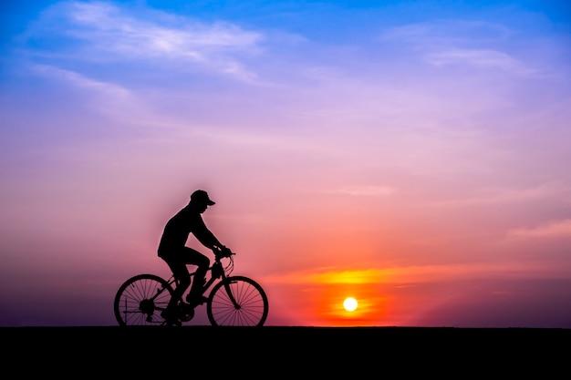 Fietser op zonsondergang achtergrond