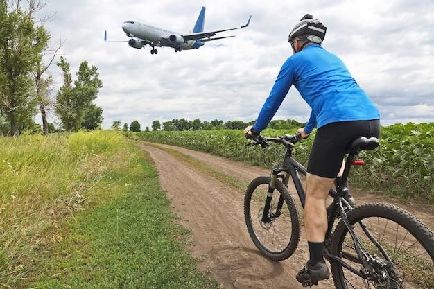 Fietser rijden langs een parcours op het vliegen van een passagiersvliegtuig