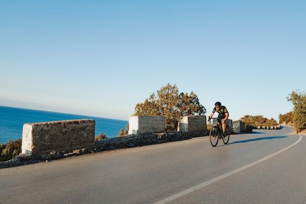 Fietser rijden op zijn fiets aan de kustweg in de ochtend