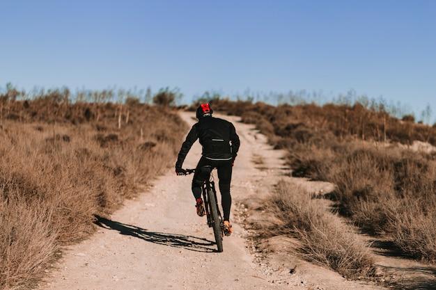 Fietser rijdt op de fiets naar beneden rocky hill bij zonsondergang. extreme sport concept.