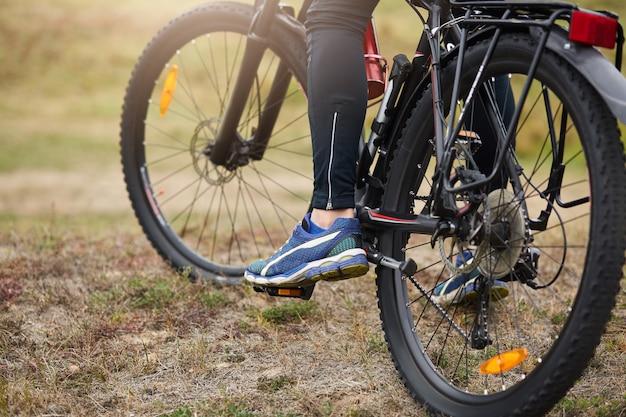 Fietser rijdt op de weg in het bos of weide, achterkant wielrenner. anonieme foto van man benen, man stopt zijn fiets