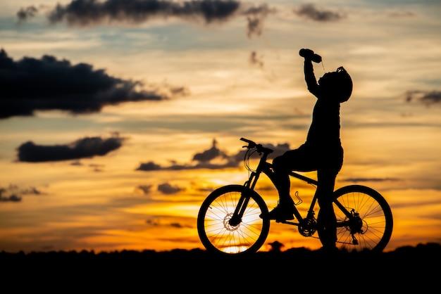 Fietser rustend silhouet bij zonsondergang. actief buitensportconcept