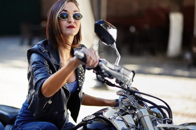 Fietsermeisje in een leerjasje op een motorfiets