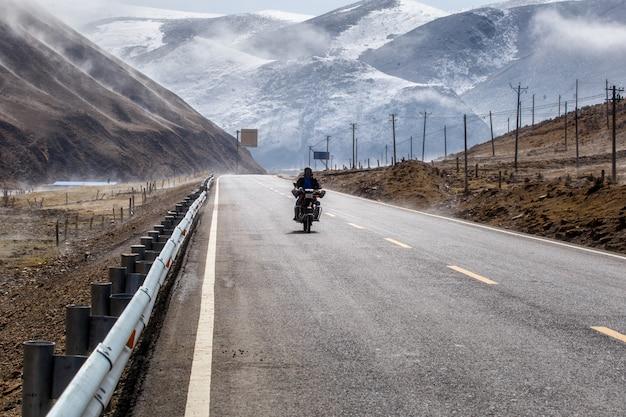 Fietsermotorfiets op de weg mooie winter in tibet onder sneeuwberg, sichuan, china