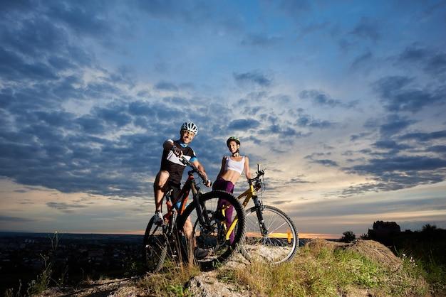 Fietsers met mountainbikes bij zonsondergang