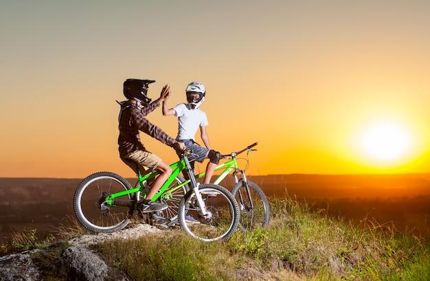 Fietsers met mountainbikes op de heuvel in de avond