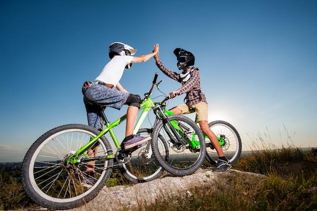 Fietsers met mountainbikes op de heuvel onder de blauwe hemel