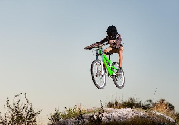 Fietsershoogspringen op een mountainbike op de heuvel tegen blauwe hemel in de bergen