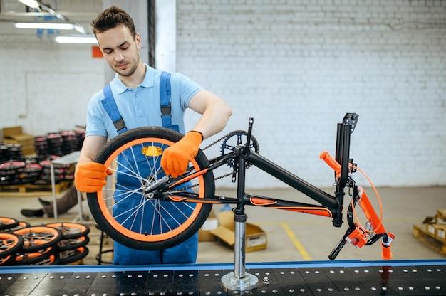 Fietsfabriek, arbeider aan de lopende band, wielinstallatie. mannelijke monteur in uniform installeert fietsonderdelen in de werkplaats