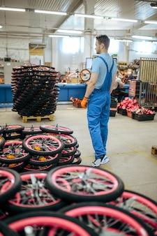 Fietsfabriek, arbeider bij de stapel fietswielen. mannelijke monteur in uniform installeert fietsonderdelen, lopende band in werkplaats