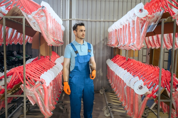 Fietsfabriek, arbeider op de rij van roze fietsframes. mannelijke monteur in uniform installeert fietsonderdelen, lopende band in werkplaats