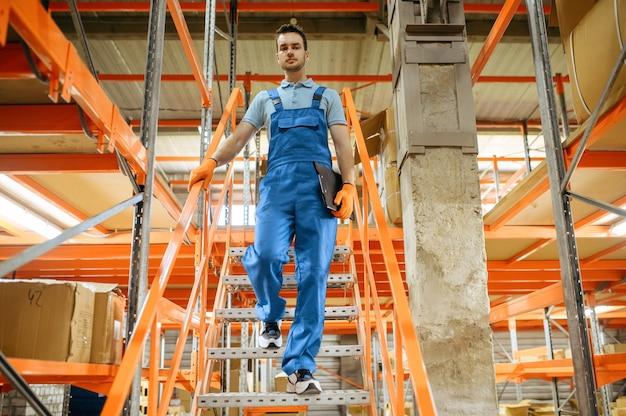 Fietsfabriek, arbeider op de trap in het fietsenmagazijn. mannelijke monteur in uniform bij de packs met fietsonderdelen