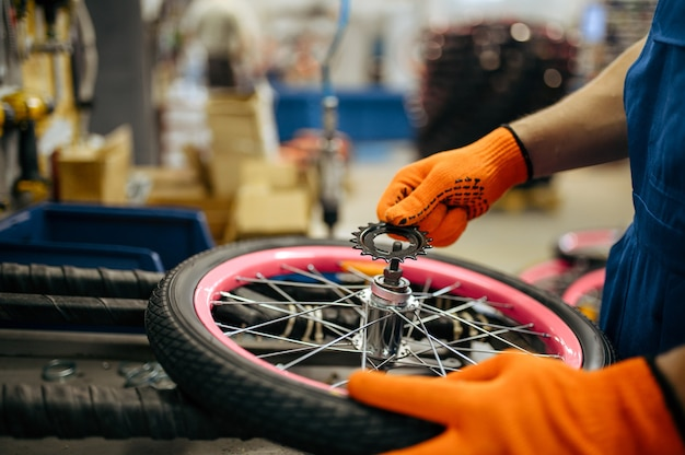 Fietsfabriek, arbeider zet de ster op het fietswiel. mannelijke monteur in uniform installeert fietsonderdelen, lopende band in werkplaats