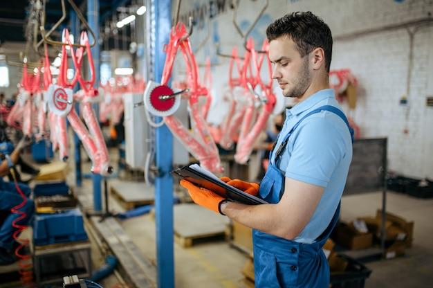 Fietsfabriek, man met notitieboekje controleert de assemblagelijn van de fiets. mannelijke monteur in uniform installeert fietsonderdelen in de werkplaats