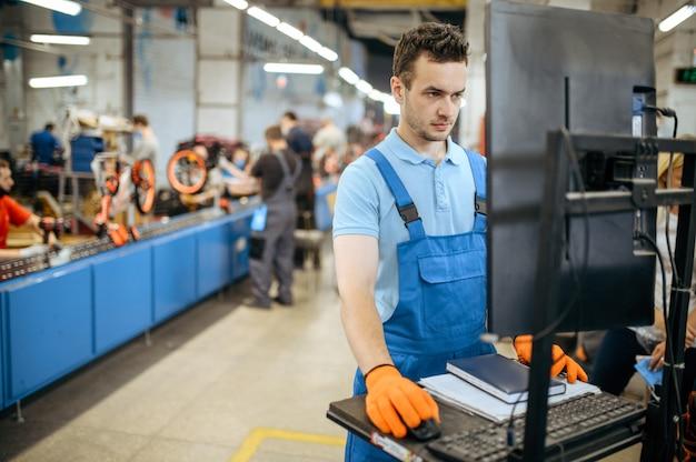 Fietsfabriek, werknemer beheert fietsassemblagelijn. mannelijke monteur in uniform installeert fietsonderdelen in de werkplaats