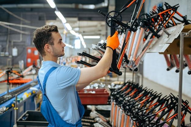 Fietsfabriek, werknemer bij de assemblagelijn van de fiets. mannelijke monteur in uniform installeert fietsonderdelen in de werkplaats
