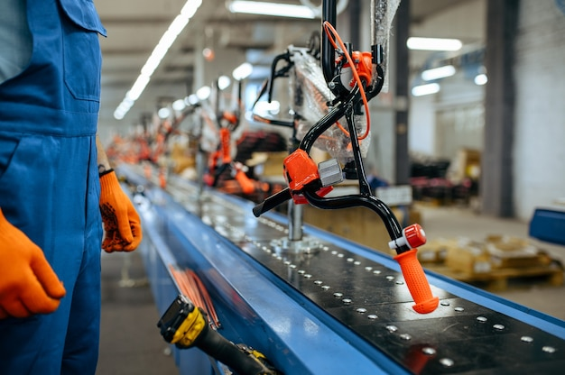 Fietsfabriek, werknemer controleert de assemblagelijn van de fiets. mannelijke monteur in uniform installeert fietsonderdelen in de werkplaats