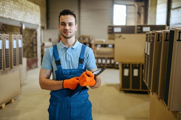 Fietsfabriek, werknemer controleert dozen met fietsen in magazijn. mannelijke monteur in uniform bij de packs met fietsonderdelen, lopende band in werkplaats