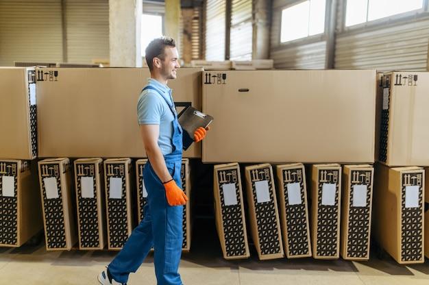 Fietsfabriek, werknemer controleert dozen met fietsen. mannelijke monteur in uniform bij de packs met fietsonderdelen, lopende band in werkplaats